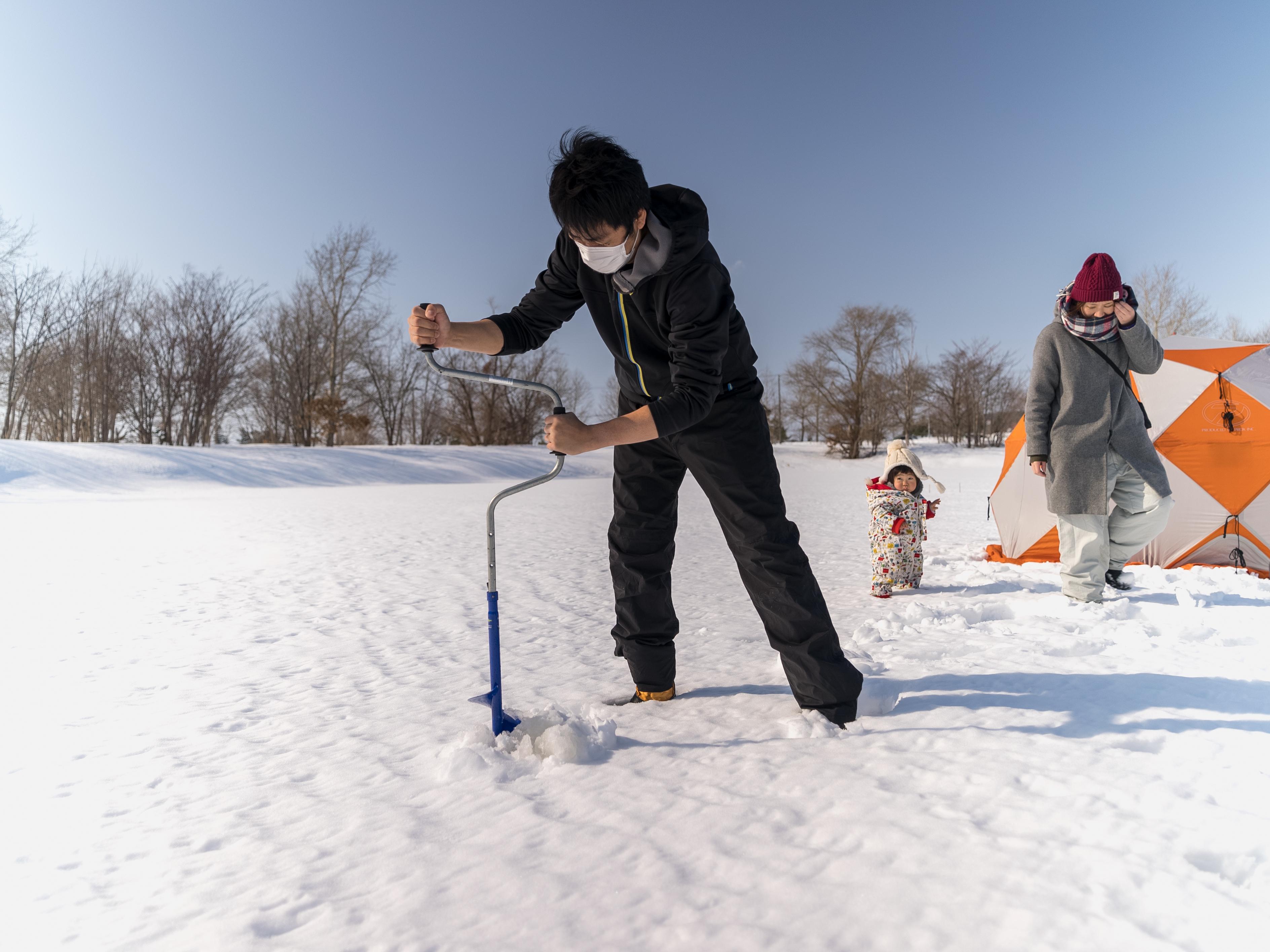 ドリルで氷に穴を開ける作業
